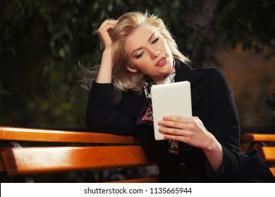 Young blond business woman using digital tablet computer sitting on the bench Stylish fashion female model wearing classic black coat