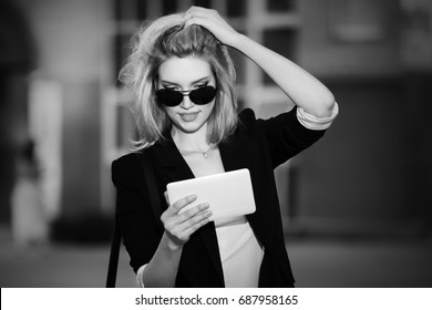 Young blond business woman using tablet computer walking in city street. Stylish fashion model in sunglasses and black jacket outdoor
