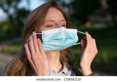 young blond Caucasian girl takes off her face mask happy to breather clean air in green summer park, concept for stopping to wear the facemasks or mask-shaming