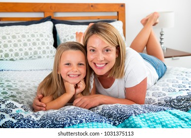 young blond Caucasian woman lying on bed together with her young sweet and adorable 7 years old daughter smiling relaxed at home bedroom in sweet mother and child lifestyle concept