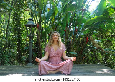 A young blond caucasian woman sitting in a meditation position with eyes open and smiling in an open air in the jungle. Young female sitting crosslegged and barefoot in a long pink dress.