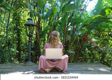 A young blond caucasian woman working on a laptop computer in an open air in the jungle sitting crosslegged and barefoot.