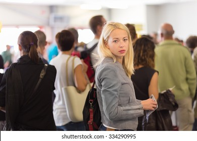 Young blond caucsian woman waiting in line with plain ticket in her hands. Lady standing in a long queue to board a plane.