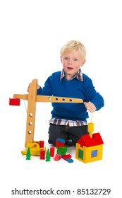 Young blond child is playing with crane and blocks