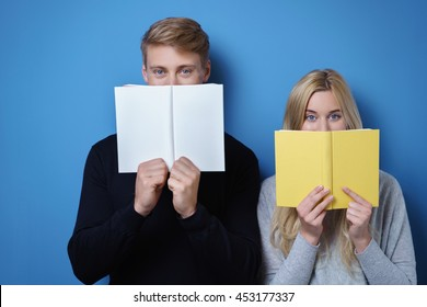Young blond couple covering their mouths with open blank white and yellow books over blue background with copy space