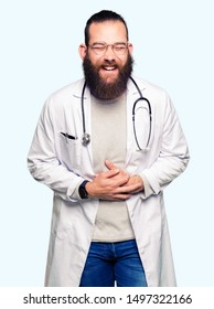 Young blond doctor man with beard wearing medical coat Smiling and laughing hard out loud because funny crazy joke. Happy expression.