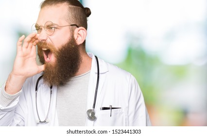 Young blond doctor man with beard wearing medical coat shouting and screaming loud to side with hand on mouth. Communication concept.
