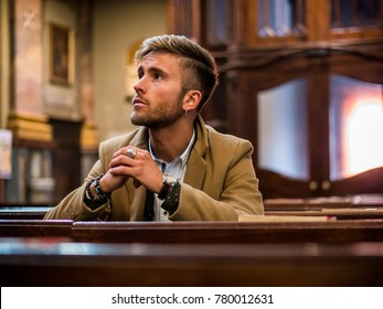 Young blond elegant man sitting in church, on wooden bench, thinking and praying, looking around