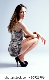 young blond fashion model in short dress on high heels, studio shot