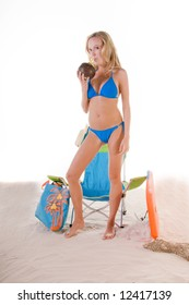 Young blond fashion model wearing a azure blue bikini standing on the beach drinking from a coconut cup