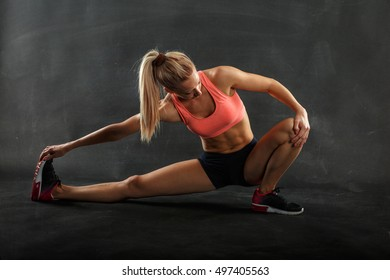 Young blond female crouching and stretching her legs.Workout.