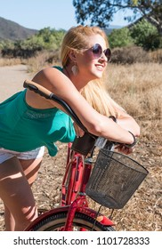Young blond female leaning over a beach cruiser bike on a ride outdoors