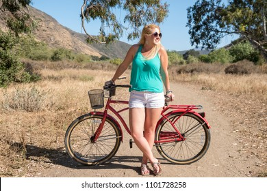 Young blond female looking off with a beach cruiser bike on a ride outdoors