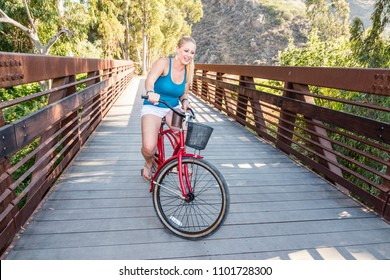 Young blond female riding a beach cruiser bike over a bridge