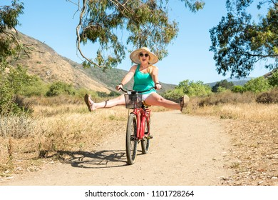 Young blond female riding a bike on a dirt tail