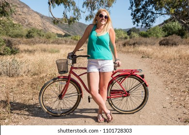Young blond female smiling with a beach cruiser bike on a ride outdoors