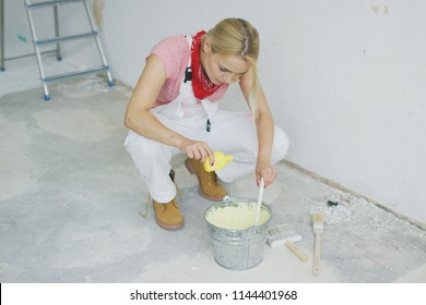 Young blond female in white overalls sitting on hunkers and pouring bright yellow paint creating beautiful pastel colored wall paint in metal bucket with brushes scattered around on floor.