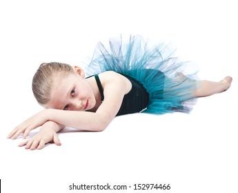 Young blond girl ballerina lying on floor in studio