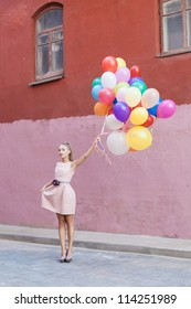 Young blond girl with balloons, urban scene, outdoors