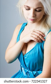young blond girl in a beautiful cyan dress sits in the studio on a white background