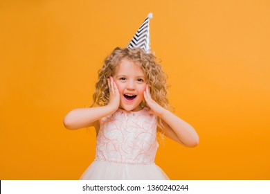 Young blond girl in birthday party princess hat hands spread up screaming isolated on a yellow background,Young beautiful girl wearing birthday cap over isolated background smiling with happy face