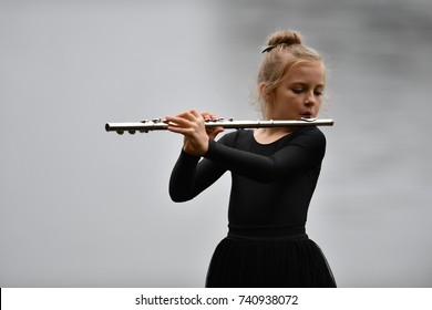 A young blond girl with blue eyes is playing flute.