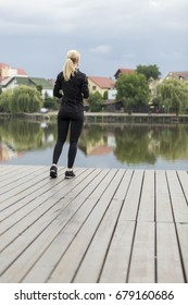 Young blond girl dressed in a sport outfit looks at a lake