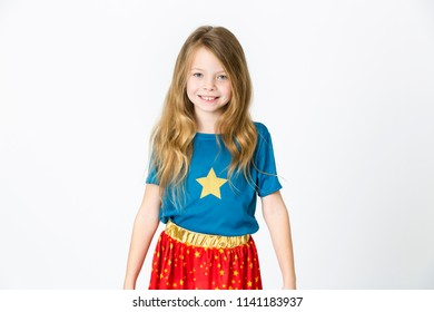 young, blond girl is dressed as a supergirl in the studio