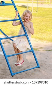 A young blond girl with green eyes looking at the camera smiling while playing on climbing bars at a park.