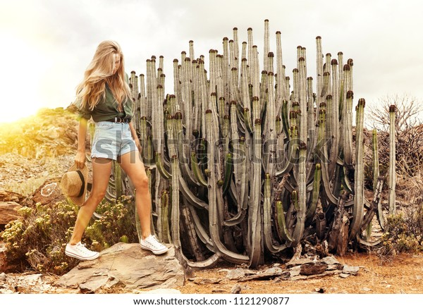 Young blond girl with long hair walking in the desert  next to  big cactus wearing jeans shorts snd dark green shirt. Sunlight flare.