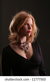 Young blond girl, looking thoughtful, with red lips, black shirt, and necklace; head and shoulders.