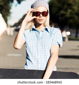 Young blond girl with plump lips sets sunglasses holding skateboard with one hand in the street on sunny day