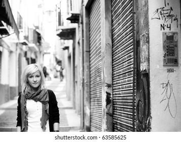 Young blond girl portrait on slum street background