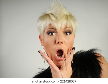 Young blond girl shouting on the camera taking off black furcoat expressive portrait