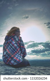 A young blond girl sit on peak and enjoy sun. Woman hiker watch sunrise or sunset while sitting on top of a mountain or on a large rock. Meditation in nature