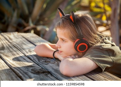 A young, blond girl sits with her chin on hands at a picnic in late afternoon light.  She is wearing headphones with cat ears on them to listen to music or block out sound due to auditory sensitivity.