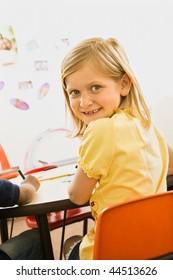 Young blond girl smiling over shoulder in elementary classroom. Vertically framed shot.