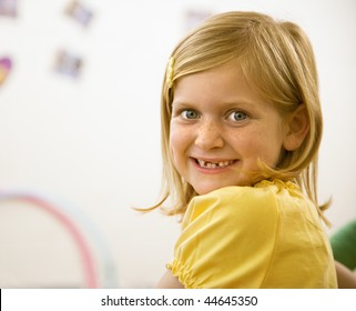 Young blond girl smiling over shoulder at viewer. Vertically framed shot.
