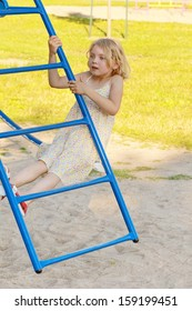 A young blond girl is startled when she loses balance and catches herself while leaning back on climbing bars at the park.