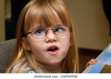 A young, blond girl with Strabismus or Ocular Palsy tries on a pair of new glasses.  Her mouth is partially open and her left eye crosses in towards her nose.