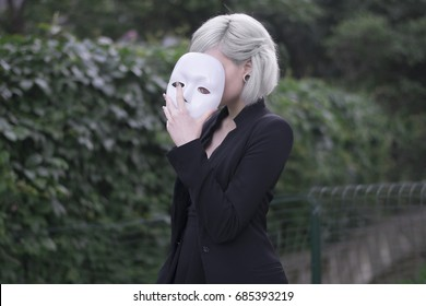 Young blond girl taking off a mask. Pretending to be someone else concept. outdoors.