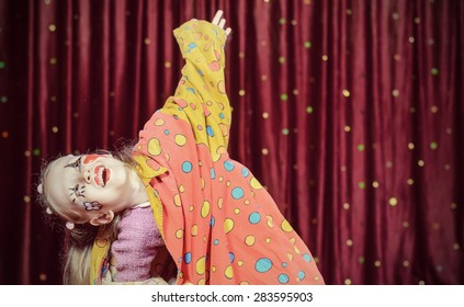Young Blond Girl Wearing Clown Make Up and Polka Dot Costume Shielding Eyes from Bright Stage Lights in front of Red Curtain