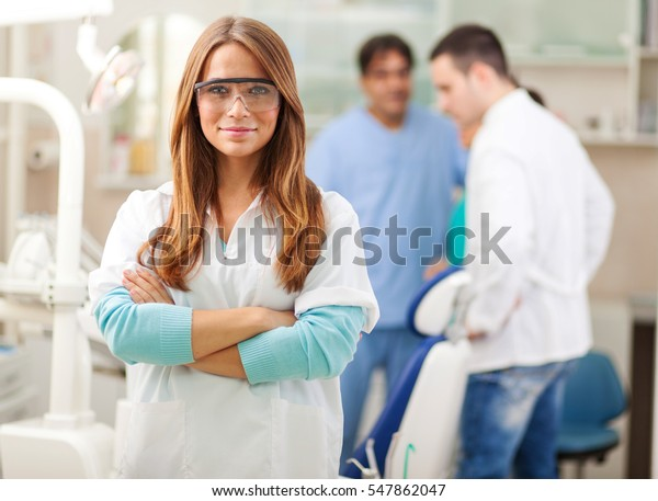 Young blond hair female dentist standing in his office and looking at camera.