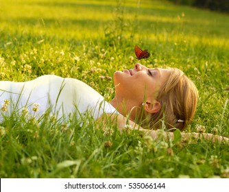 Young blond hair female lying down on grass.Butterfly standing on her nose.