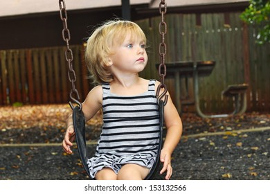 A young blond haired, blue eyed girl looks up from her swing, watching the other children swimg up high thinking about how they do that.