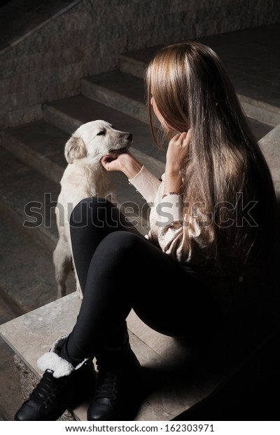 Young blond haired woman outdoor with dog together. Pet adoption concept. Homeless dog is waiting for you in shelter, adopt it!