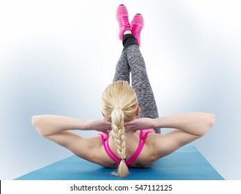 Young blond haired woman performing yoga on blue exercise mat.