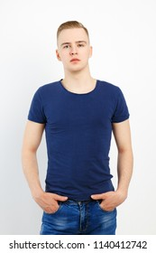 Young blond handsome man in blue shirt and jeans poses in white studio
