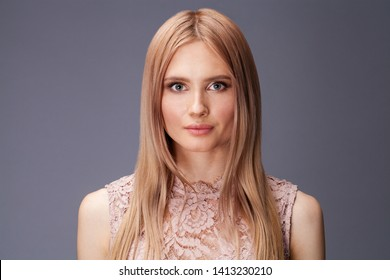 Young blond lady in sexy dress posing on grey background