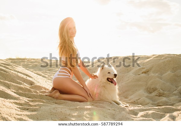 Young blond with long hair posing in the sunlights with samoyed on the nature, on the beach in white lace underwear at summer time